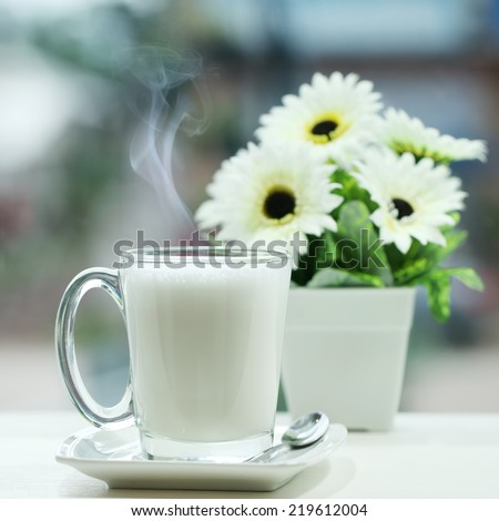 Hot milk in a glass with Flowers - stock photo