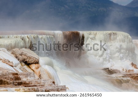 Hot mineral water cascading over stalactite formations with steam rising against the mountains at Yellowstone National Park. - stock photo