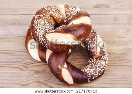 hot mixed pretzels topped by sesame seeds over wooden table