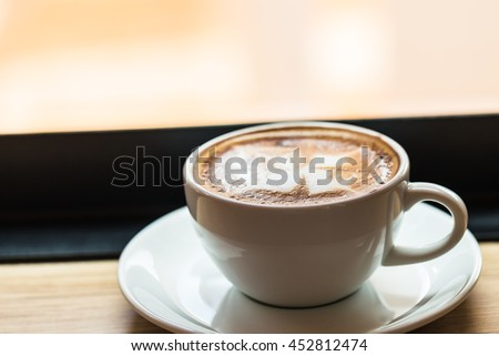 hot mocha coffee with flower pattern in a white cup at sunrise time