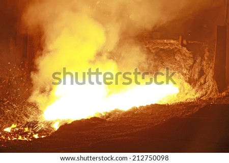 hot molten iron flowing from blast furnace, closeup of photo - stock photo