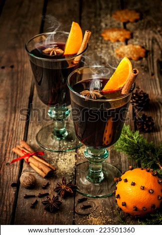 Hot mulled wine in a glass with orange slices, anise and cinnamon sticks on vintage wood table. Christmas or winter warming drink with recipe ingredients around. - stock photo