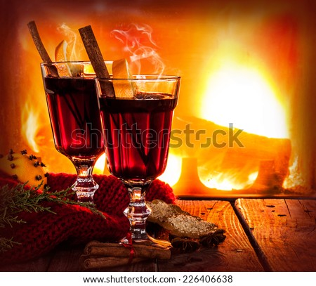 Hot mulled wine in a glass with orange slices, anise and cinnamon sticks on vintage wood table. Fireplace  as background. Christmas or winter warming drink. Layout with free text space. - stock photo