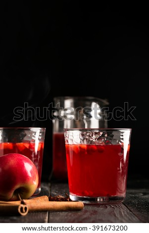Hot mulled wine prepared with fruits and various spices. Black background
