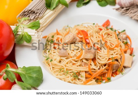 hot noodles with vegetables and garnish on white plate