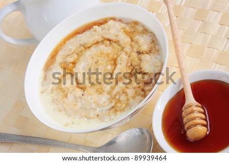 Hot oat porridge breakfast with cream and honey.