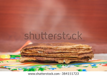 hot pancakes on the plate on the bright colorful tablecloth