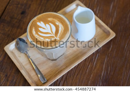 Hot Piccolo latte coffee serve with syrup in wood tray on wooden table. - stock photo