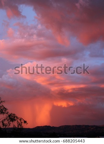Hot pink fuchsia and gray monsoon clouds with red rain down pour at sunset over the Catalina mountains in silhouette in the Tucson Arizona desert