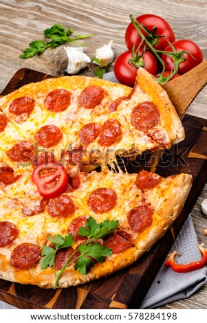 Hot pizza on wooden background. Toned image