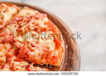 Hot pizza slice with melting cheese on a white granite stone table.  - stock photo