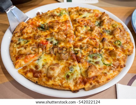 Hot pizza slice with melting cheese on dish