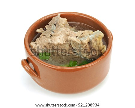 Hot pork ribs soup with parsley leaves on a white background