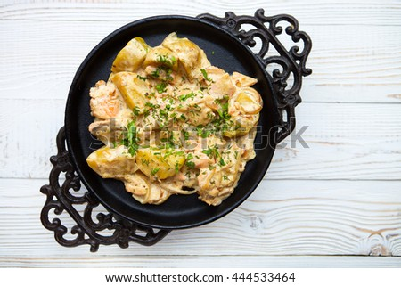 Hot potatoes and red fish in creamy sauce giving in a pig-iron plate on a white wooden background - stock photo