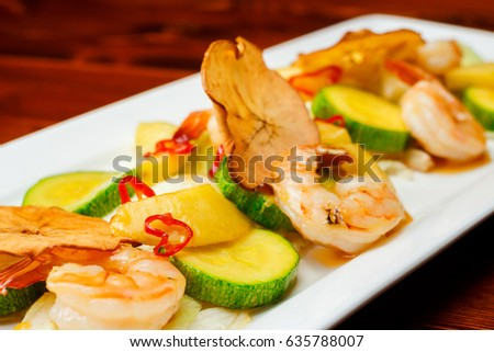 Hot prawn salad with potatoes, zucchini and sweet honey sauce