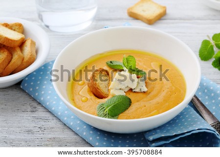 hot pumpkin cream soup with cheese in white bowl - stock photo