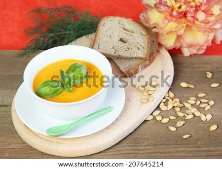 Hot pumpkin soup and slices of bread  on a table - stock photo