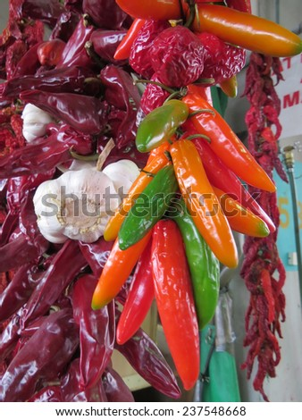 Hot red and green peppers and garlic hang at a farmers' market - stock photo