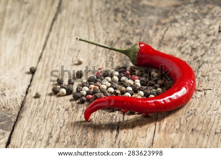Hot red chili pepper and colorful peppercorns on a wooden table, selective focus - stock photo