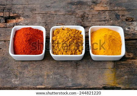 Hot red chili powder, curry and turmeric powder on wooden background - stock photo