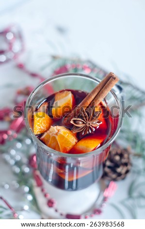 Hot red mulled wine isolated on white background with christmas spices, orange slice, anise and cinnamon sticks, close up. - stock photo