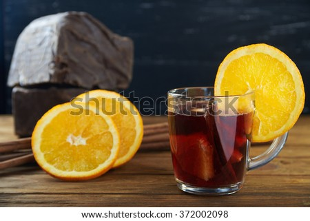 Hot red mulled wine with fruits, cinnamon sticks with big piece of black chocolate on background on a wooden table  - stock photo