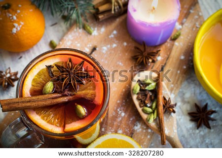 Hot red mulled wine with honey, orange slices, ginger, cardamom, cloves, anise and cinnamon sticks. Christmas decorations, close up. - stock photo