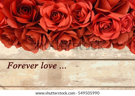 "hot red paper rose on old wooden background with "" Forever Love"" word"