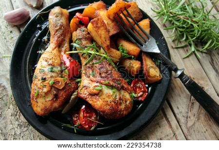 Hot roasted chicken legs with fried potatoes  - stock photo