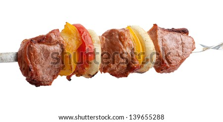 Hot roasted meat with onion, tomato and pepper on the metal skewer - stock photo