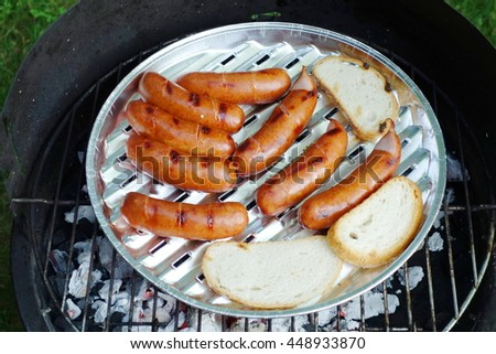 Hot roasted sausages and sliced bread on grill, barbecue. Closeup view from above.  - stock photo
