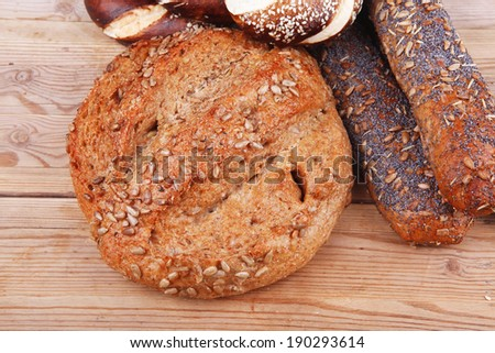 hot rural french round rye bread and baguette topped with sunflower seeds and sweet bagels on wooden tables - stock photo