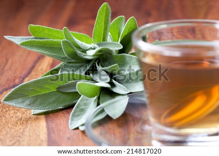 hot sage tea with silver spoon inside tea cup, wooden floor, bunch of sage in background - stock photo