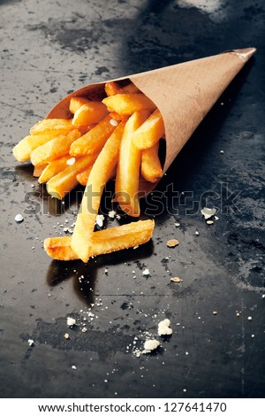 Hot salty fried potatoes in a paper cornet, close up - stock photo