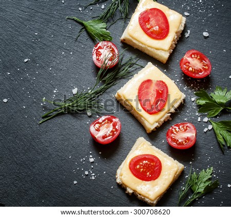 Hot sandwiches with cheese and tomato, greens, on a dark stone background, top view, selective focus - stock photo