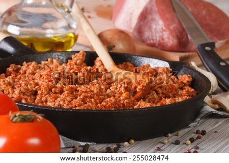 hot sauce Bolognese in a frying pan and fresh ingredients close-up on the table. horizontal