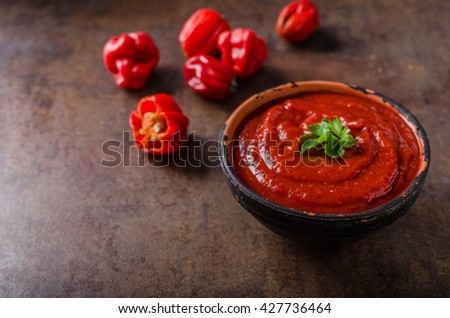 Hot sauce from chilli peppers and tomatoes, parsley on top - stock photo