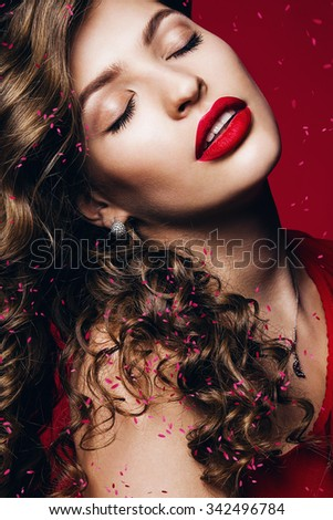 hot sensual woman with red lips and pink petals on red background