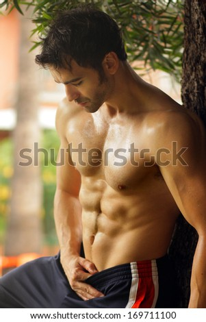Hot sexy fit man leaning against tree - stock photo