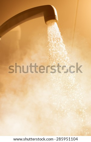 hot shower with flowing water and steam - stock photo