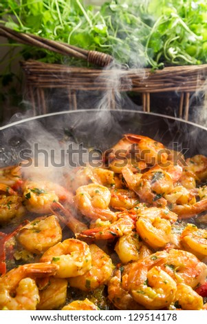 Hot shrimp fried in a pan with herbs - stock photo
