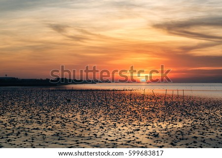 Hot sky with red cloud at sunrise over the sea near coast in Thailand.