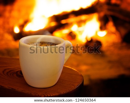 Hot smoking coffee by fireplace - stock photo