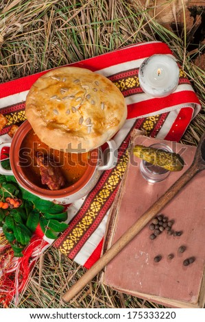 Hot soup with meat in a pot with bread cover