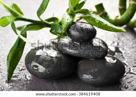 Hot spa stones with bamboo on grey background, close-up