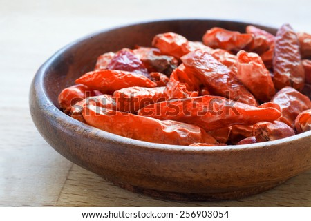 hot spice, dried red chili in a wodden bowl, closeup - stock photo
