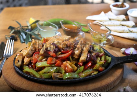 Hot spicy chicken fajitas with vegetables in casserole