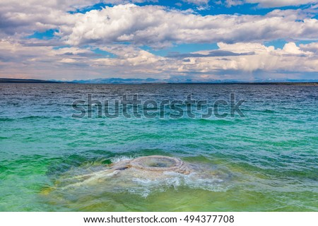 Hot springs and hydrothermal vents have swirling patterns in the water just offshore. Fishing Cone at the shore of Yellowstone Lake. West Thumb Geyser Basin, Yellowstone National Park, Wyoming