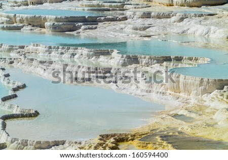 Hot springs create cascades and travertines of calcium running down hillside in Pamukkale in Turkey