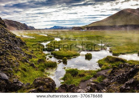 Hot steam over the source of the thermal waters. Sunrise Park Landmannalaugar. White nights in Iceland - stock photo